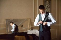 Groom prepares for his wedding in black and white tuxedo attire.