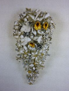 """The Queen hasn`t been seen wearing this brooch yet, it looks like a copy of her Coronation bouquet which featured orchids. It was a predominately white bouquet with Cattleya, Odontoglossum Crispum orchids (some of which had golden centres), white roses, carnations, stephanotis & lily of the valley with a touch of asparagus fern for greenery. The brooch seems to be made of white & yellow gold with a few diamonds for sparkle. The brooch is pictured in Angela Kelly`s book """"Dressing the Queen""""."""
