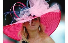 KENTUCKY DERBY 2013 | A woman makes her way to her seat before the running of the 139th Kentucky Oaks at Churchill Downs Friday, May 3, 2013, in Louisville, Ky. | Photograph by: Darron Cummings, AP