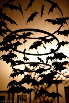 DIY Halloween bat chandelier using sewing frames, acrylic paint, thin sheets of compressed foam, string, fishing line, and electrical tape.