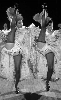 dancers, flipping their skirts to show garters & black stockings, perform on stage at the Moulin Rouge nightclub.   — pinterest.com