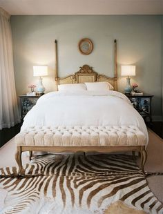 zebra hide layered rug in bedroom