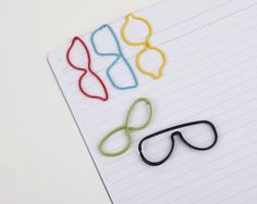 """These """"spec"""" shaped  #paper #clips by Umbra are a great way to add a little fun to your work day and liven up those never-ending stacks of paper.  - http://thegadgetflow.com/portfolio/specs-paper-clip/"""