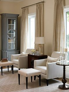 Double Duty | Sarah Richardson Design - A pair of footstools in front of armchairs in the living room can double as coffee tables when used with a tray, provide extra seating for a crowd, or create the perfect spot to put up your feet and enjoy a fire and a good read. #neutrals #windows