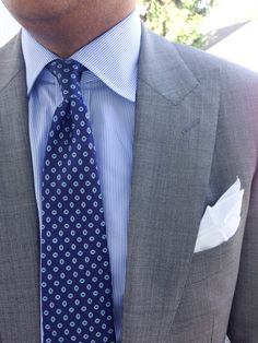 Light grey suit with peak lapels, white shirt with light blue stripes, blue tie with white & green medallions