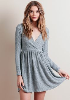 Classic with a slight edge, this knit dress is designed in a marled gray hue and ribbed detailing for added texture. Featuring a sexy surplice neckline, long fitted sleeves, and an elastic wais...