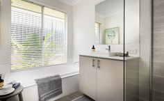 The large main bathroom features a semi-inset vanity basin, Caesarstone benchtop and bath