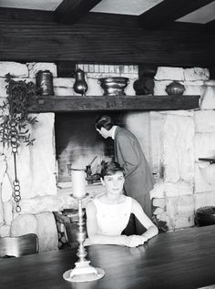 "The actress Audrey Hepburn photographed with her husband Mel Ferrer (actor, dialogue coach and film director) in the rustic kitchen of ""Villa Bethania"", their villa in Bürgenstock (Switzerland), in June 1955.Audrey was wearing:Cocktail dress: Givenchy (specially for an afternoon cocktail, sleeveless, of grosgrain in a shade of light pink with some white stripes, detail of buttons of resin in the front, skirt with pleats starting from the hip line, length below the knees, liner of light pink…"