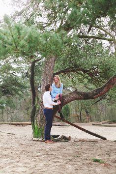 stel staat bij elkaar en lacht  naar elkaar in het bos terwijl zij in de boom zit