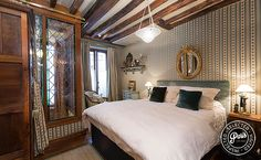 The master bedroom has a painted bed frame, queen-size bed, ornate armoire, windows, comfortable side chair, and several artistic touches.