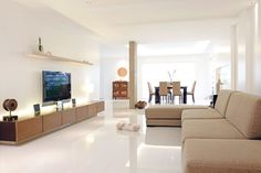 White walls expand the space of the living room. Light-colored furniture seems to float amid an area flooded with light. Clean lines delineate space and lead the eyes outwards, creating an illusion that the room is larger than it seems.