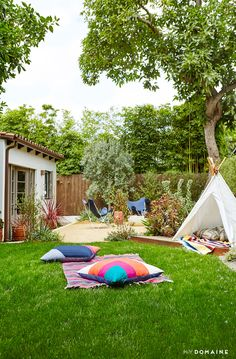 Teepee in backyard with colorful pillows