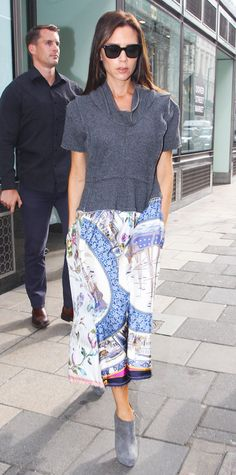 In a very posh-like fashion, Victoria Beckham stepped out in a charcoal gray cowl-neck top that she paired with flowy printed shin-grazing skirt and gray booties. #InStyle