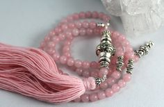 If you love Rose Quartz and the colour pink, this is the perfect mala necklace. The guru bead with its silky pink natural bamboo fibre tassel is a perfect match to the Rose Quartz beads.  Pictured with 108 counter beads 6mm size Rose Quartz . The photos show a 6mm colour enhanced Rose Quartz…. currently this item is only available in natural, undyed Rose Quartz beads which are slightly paler in colour. Total length with 6mm beads is approx. 30 inches, excluding the 4 inch tassel and focal…