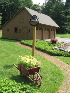 Charming Colonial-style garage and brick walkway... Love the dinner bell and cute wheelbarrow too!