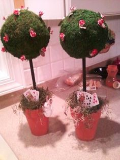I bought the moss covered balls pre-made, then added dowel rods, which I stuck into foam in the clay pots. Add some spanish moss and fake roses, and voila!