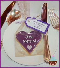 "#purple wedding tables ... Heart shaped iced biscuit favours with ""Just Married"" iced onto the deep purple sugarpaste with a pale lilac heart.   A thank you message was printed onto the favour tag. (The tag looks blue in this picture, but was actually the same colour as the bis Please don't miss our great wedding favor ideas at www.CreativeWeddingStyle.com"