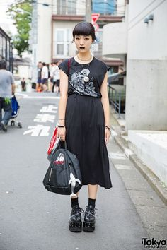 17-year-old Chikio on the street in Harajuku wearing all black fashion (mostly resale) with black lipstick, a Vivienne Westwood armor ring, and black platform creepers with chains and studs.