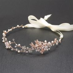 "Hand-painted metallic leaves, Swarovski crystal flowers and freshwater pearls are entwined with wire creating a breathtaking rose gold bridal headpiece. The flexible vine tiara headband has 14"" of delicate floral sprigs and 16"" double ribbons on each side."