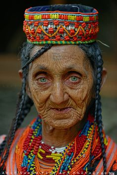 An elderly woman from Pakistan with an impassive expression, yet intense pale green eyes in her colorful headdress, & bead necklaces