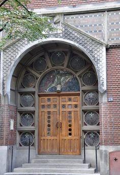 Une porte latérale de l'église entourée des vitraux de Jacques Gruber.Église Saint-Christophe-de-Javel. Paris XV