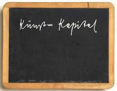 slate board with white silkscreened text Kunst=Kapital in wooden frame, with...