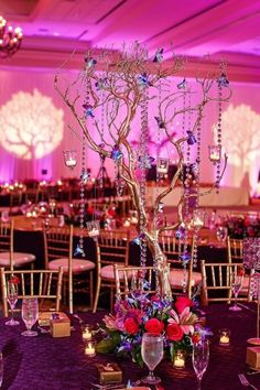 Paint artificial branches gold and decorate in crystals, orchids and hanging candles to recreate this gorgeous centerpiece found on http://www.indianweddingsite.com/blue-purple-orchid-themed-indian-reception/