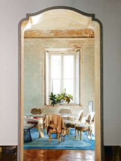 House tour: a Milanese palazzo beautifully stripped back to its roots: Inthe main dining room, 'DC1505' table by de Cotiis; mix of  antiqueVenetian and Knoll chairs; vintage rug.