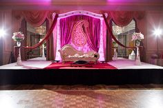 pink/purple and white indian wedding stage, with deeply colored uplighting