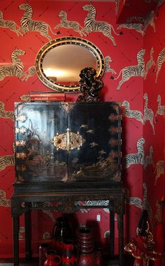 Asian inspired home deco Scalamandre zebra wallpaper behind antique chinoiserie cabinet