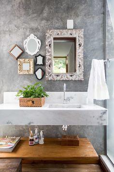 Um lavabo super iluminado, com parede em cimento queimado, numa casa contemporânea
