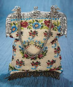 French Beadwork Purse with Silver Frame. A silver frame with richly-sculpted floral designs and swan clasps for the silver bead chain has heavily beaded bag with gold beads and a blue and red floral design.  Circa 1840. http://Theriaults.com/