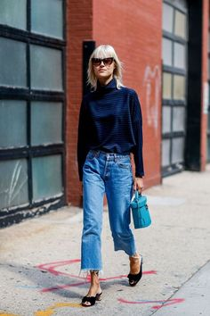 flare cut off jeans, navy turtle neck, slides, blue bucket bag, retro shades