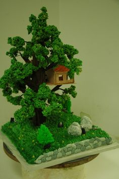 """Treehouse - Cake for a boy who wanted a treehouse with """"spy things."""" The cake was the ground, the leaves are rice krispy treats died green, the treehouse was gumpaste.  Tree was a dowel rod, wire structure with chocolate icing bark."""
