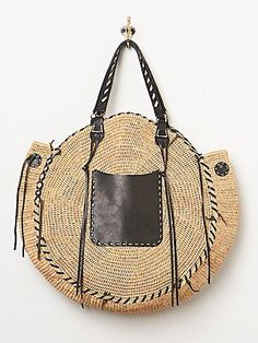 Circular woven tote with black leather accents.