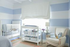 White and blue nursery features, white and blue horizontal striped walls framing traditional white crib