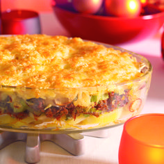Verhit de boter en olie in een koekenpan en bak het gehakt snel korrelig en gaar. Schep als het gehakt bijna gaar is de plakjes champignon er doorheen en bak even mee. Schep het gehaktmengsel met het braadvet in een kom, roer de preiringen erdoor en breng op smaak met zout, peper en nootmuskaat. Laat dit mengsel afkoelen. Klop vervolgens de eieren en peterselie door het gehakt. Smeer de bodem van een ronde of rechthoekige vuurvaste schaal dun in met zonnebloemolie. Bedek de bodem met de…