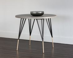 MIDORI DINING TABLE - Round dining table with a concrete top, supported by thin black metal legs and stylish brushed antique brass feet.