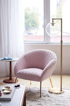 Upholstered in plush, quilted velvet that's set in relief by sleek brass legs, this chic chair offers a thoughtful balance of warm and cool.