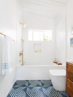 Bright modern bathroom with white walls, gold accents, and brightly printed blue tiles