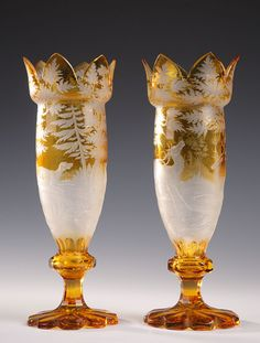 A pair of Bohemian yellow crystal vases decorated with hunting scenes depicting deer and dogs in the wild. Every vase rests on a high foot with wavy edges. The exceptionally...