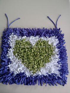 """Cubre Silla """"Dalia"""".  Cubresilla rectangular confeccionado con flecos de totora lisa en tonos violeta (para el marco y lazos de sujecion), blanco (para el centro) y verde manzana (en el corazón).  Medidas: 40x47cm."""