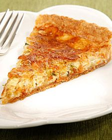 CARAMELIZED LEEK QUICHE  All-purpose flour, for work surface  1/2 recipe Pate Brisee  2 tablespoons extra-virgin olive oil  3 leeks, whites and light green parts only, halved lenthwise, sliced crosswise 1/4-inch thick  2 teaspoons fresh thyme leaves  Coarse salt and freshly ground pepper  1 1/2 cups freshly grated gruyere cheese  3 large eggs  1 large egg yolk  1/2 cup milk  1/2 cup heavy cream