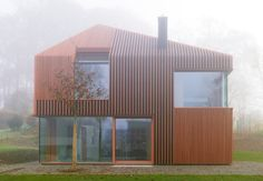 """Residential Architecture: House 11×11 by Titus Bernhard Architekten: """".. there are no horizontal crossbeams to interrupt the vertically striped wooden batons that clad this house..Matching wooden slats frame the building's deep-set windows, which fold around the corners of walls as well as up over the concealed eaves..The structure below the wooden cladding is constructed from prefabricated elements that were assembled onsite…""""  Interesting wood-lamella vertical cladding, ample glazing…"""