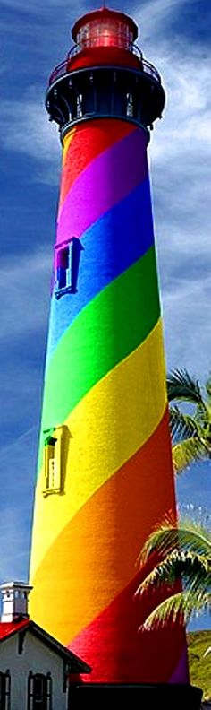 """Rainbow color swirl lighthouse  [per SailorGil on Tumblr:  """"I went back to Flickr where I found the photo … It is the St Augustine lighthouse in Florida, which has black and white stripes … The photographer has used photoshop to do the rainbow stripes.""""]"""
