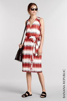 Get obsessed with this pretty in plaid, sleeveless red and white wrap dress with a tie-front belt and ruffle trim. Make it the perfect dress for a summer day by pairing it with chic sunglasses, flat sandals and a bucket bag to carry your summer reading. Shop now at Banana Republic.