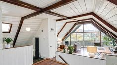 The two-bedroom, 1,136-square-foot boathouse features a master bedroom with an inward-sloping exterior glass wall that resembles the side of a boat's hull.