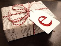 Newspaper, baker's twine, Monogram SO much cheaper than wrapping paper.Have been doing this for years.