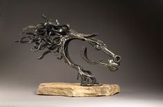 Traditional blacksmith forged reclaimed steel including horseshoes on a stone base.