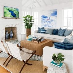 """The living room is filled with a mix of collected items: a vintage dhurrie atop a sea grass rug, a pair of Hans Wegner chairs, and a vibrant surf painting. The marble fire-place surround """"has an elegant feel to it,"""" says Keenan, """"but it's not polished, so"""
